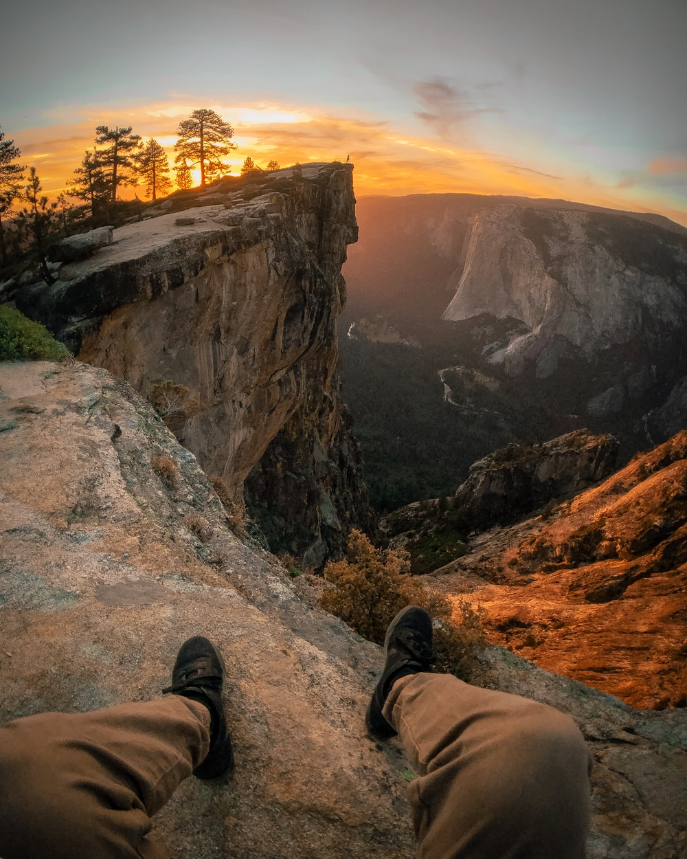 person pair of shoes and sitting on edge of mountain
