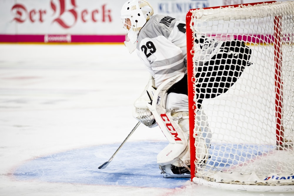 person guarding goalie net in field