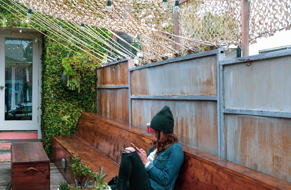 woman sitting on bench while using phone during daytime
