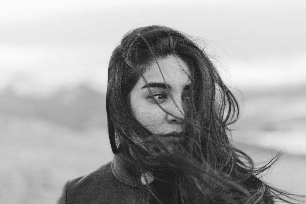 grayscale photography of woman covered her face with hair