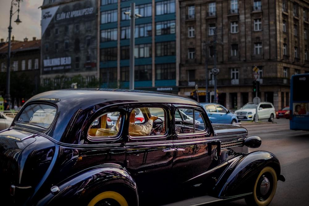 vintage black vehicle on road during daytime