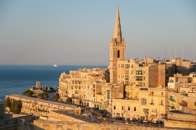 brown concrete cathedral near sea during daytime malta teams background