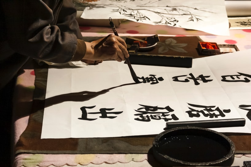 A person's hand writing Chinese calligraphy on a large sheet of paper.