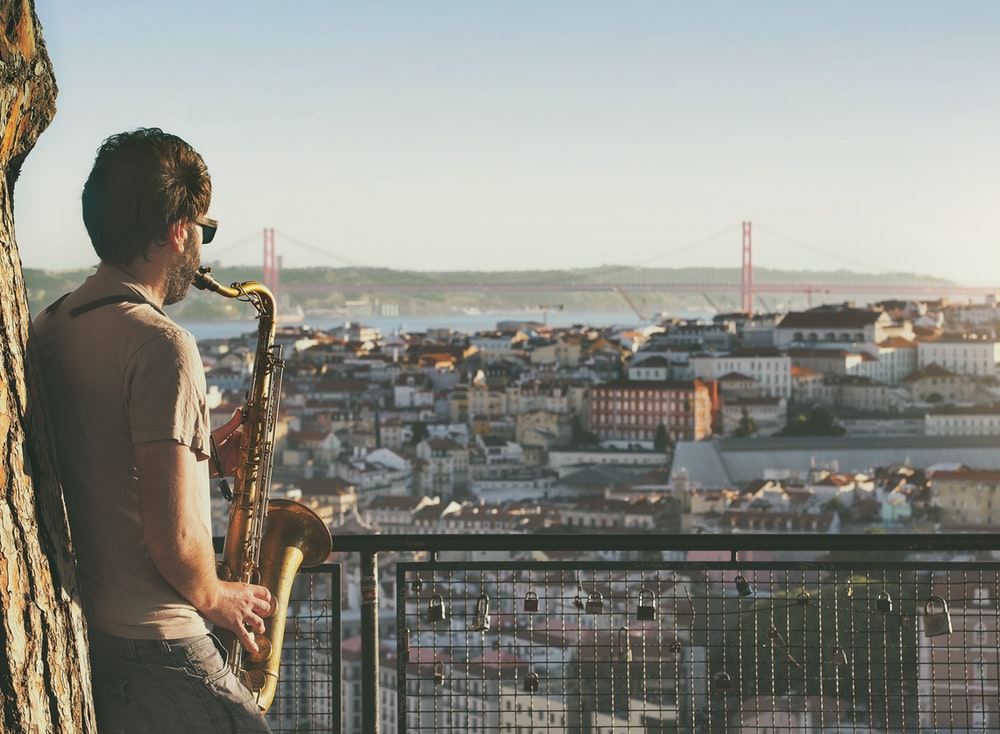 man playing saxophone on terrace overlooking city during daytime