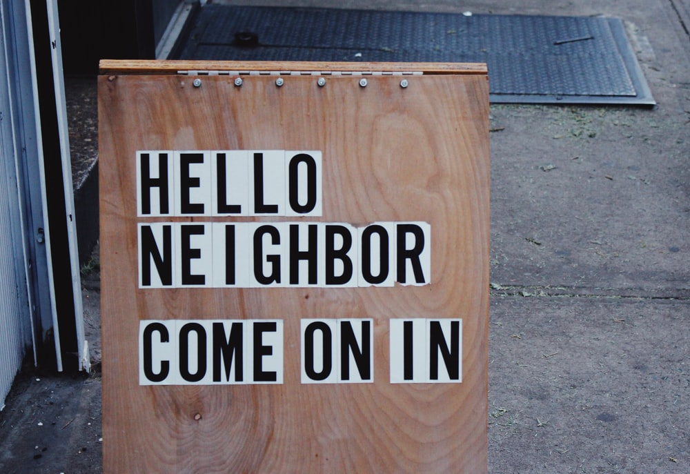 brown wooden board with hello neighbor come on in signage