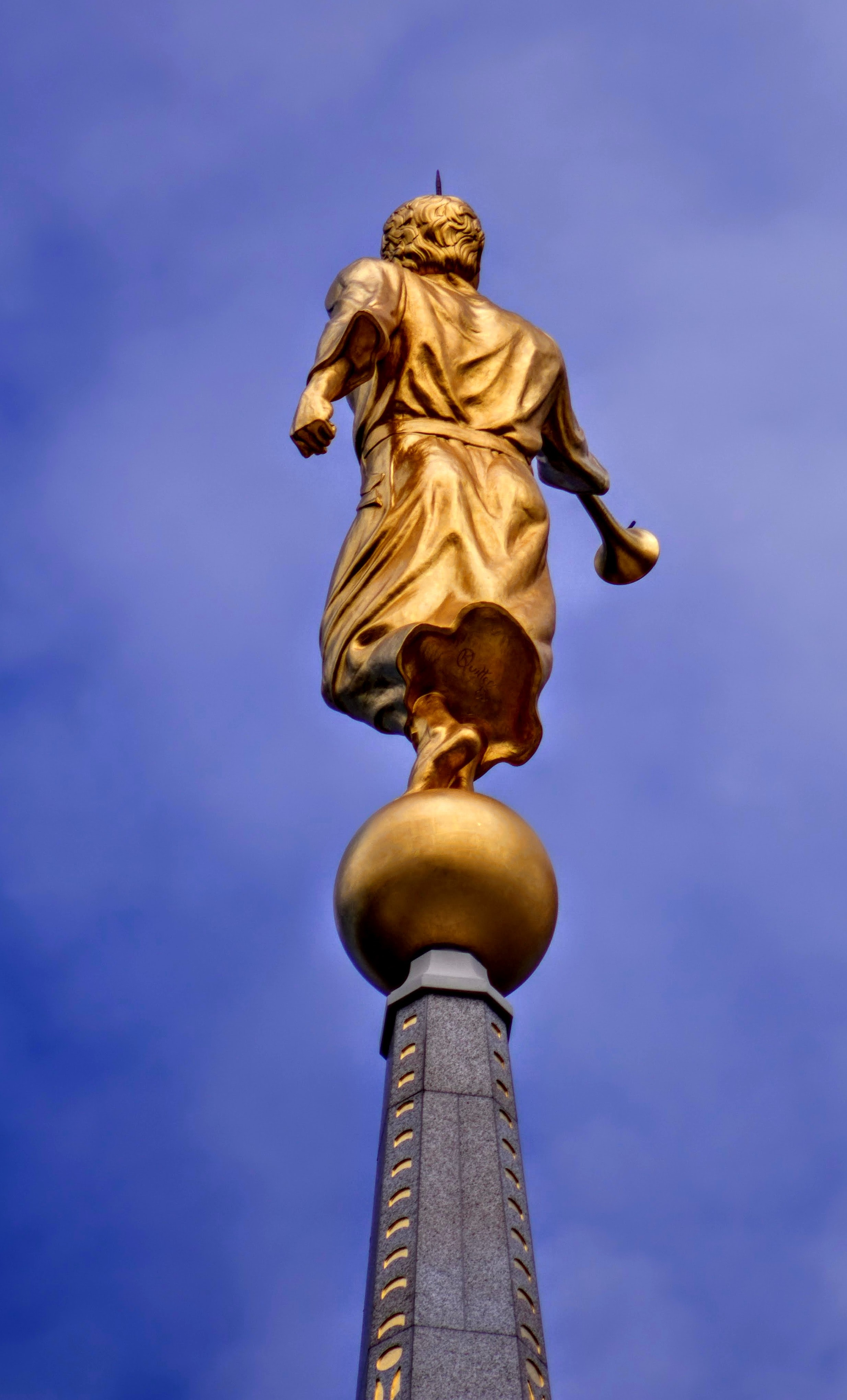 low-angle photography of man statue under clear blue sky