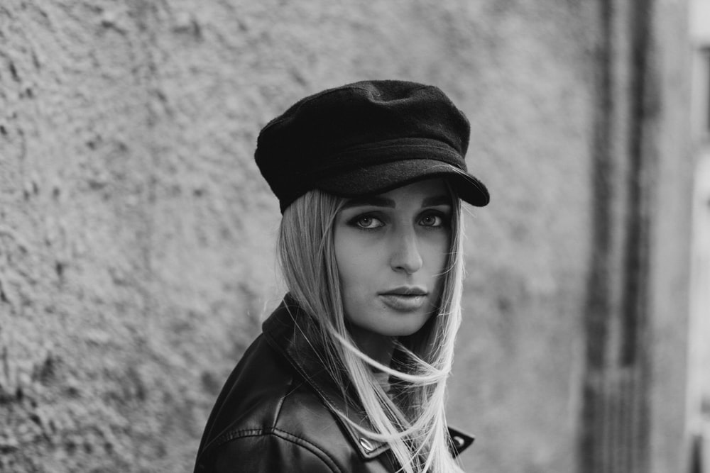 grayscale photo of woman wearing cap beside wall