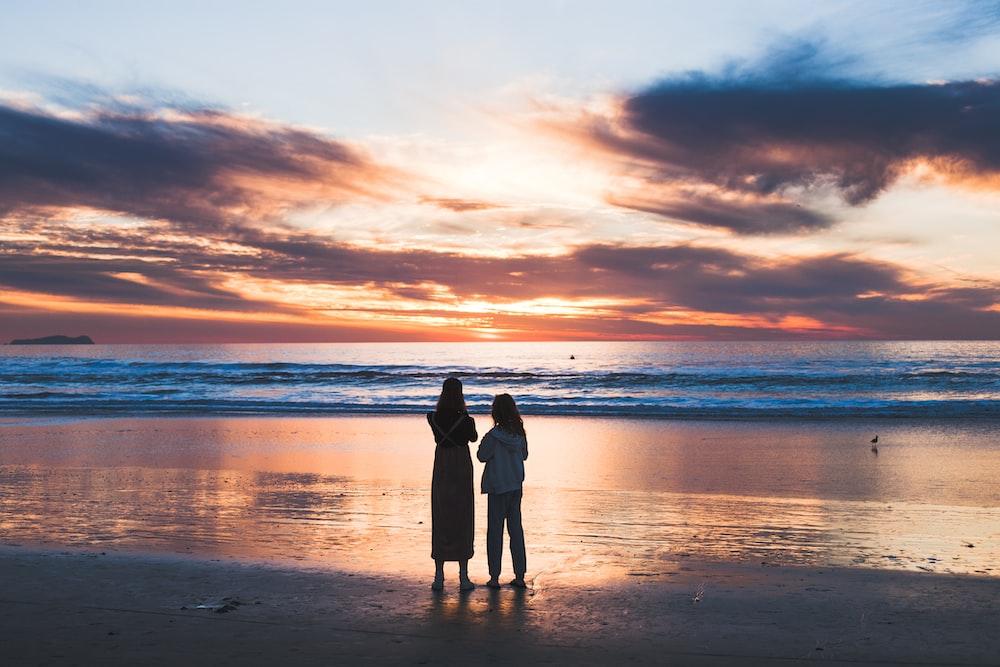 woman and girl standing on seashore