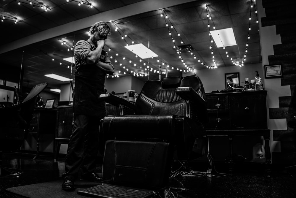 gray scale photo of man inside barber shop