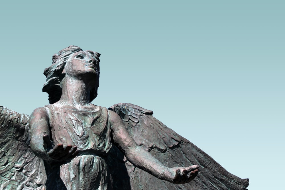 female angel looking up with both hands open statue