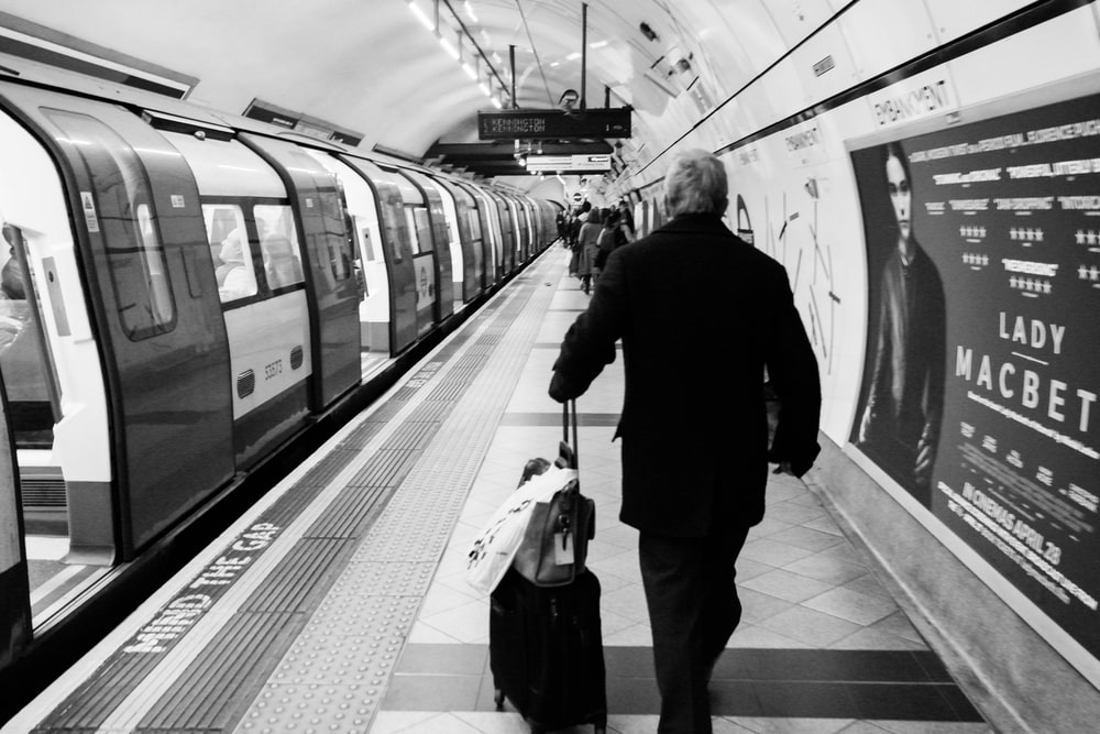 man with trolley bag walking in train station grayscale photo