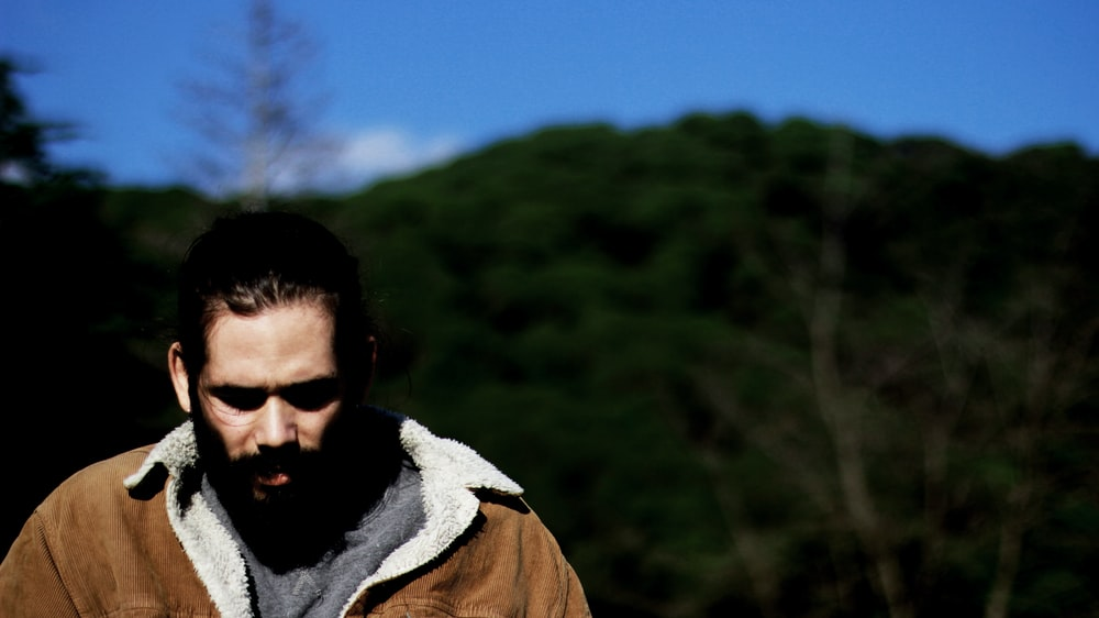 man wearing brown coat walking on forest