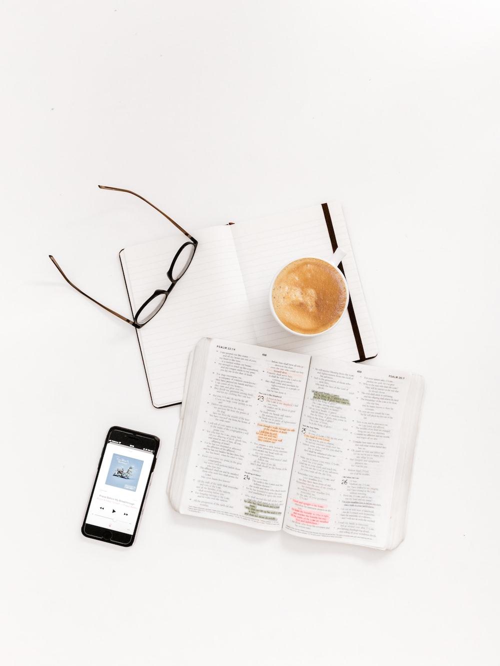 black framed eyeglasses, notepad teacup and smartphone