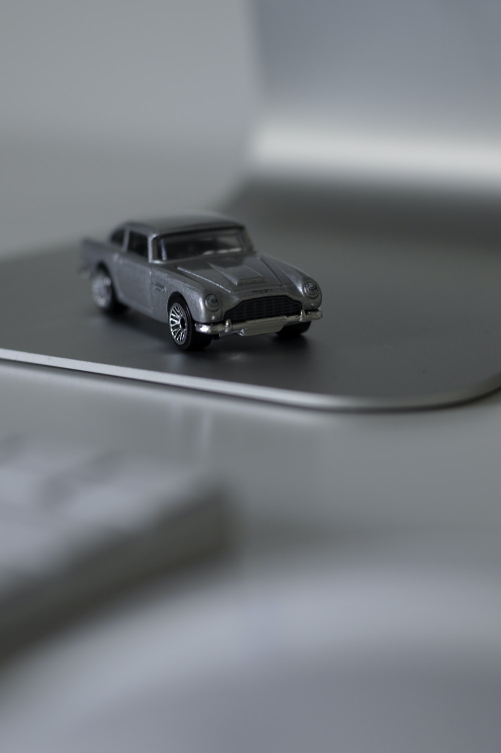 shallow focus photography of silver die-cast car model