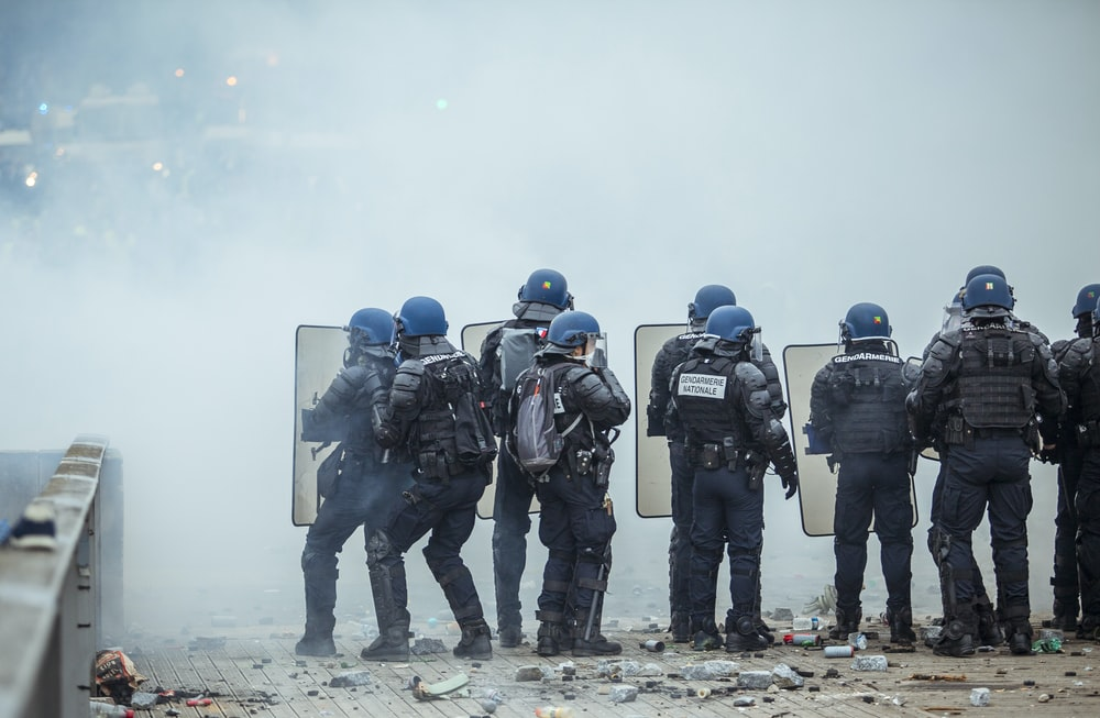 riot police holding shield in front of smoke
