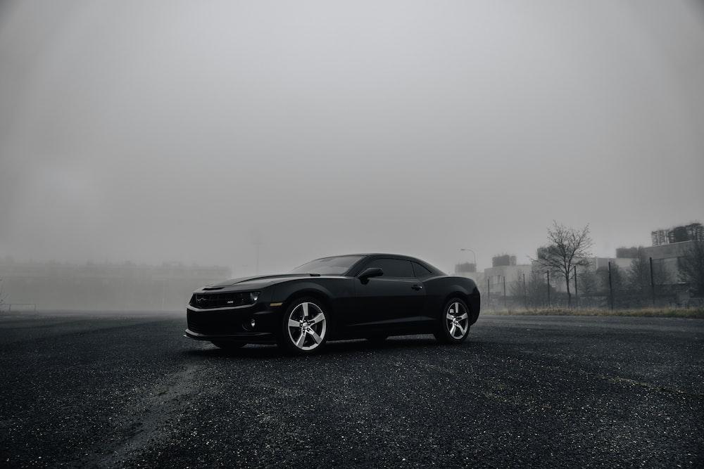 black Dodge Challenger on road during foggy day
