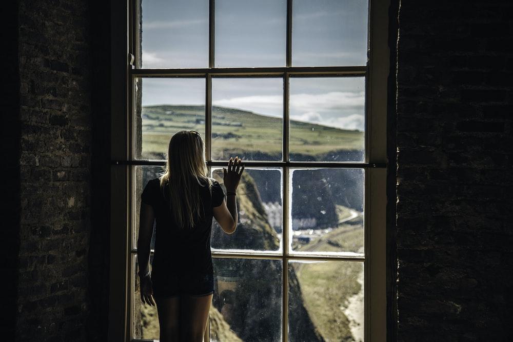 woman looking outside glass window
