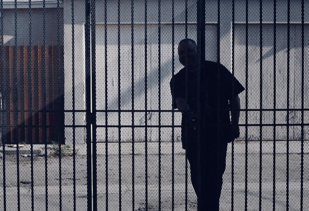 man trying to open metal gate during daytime