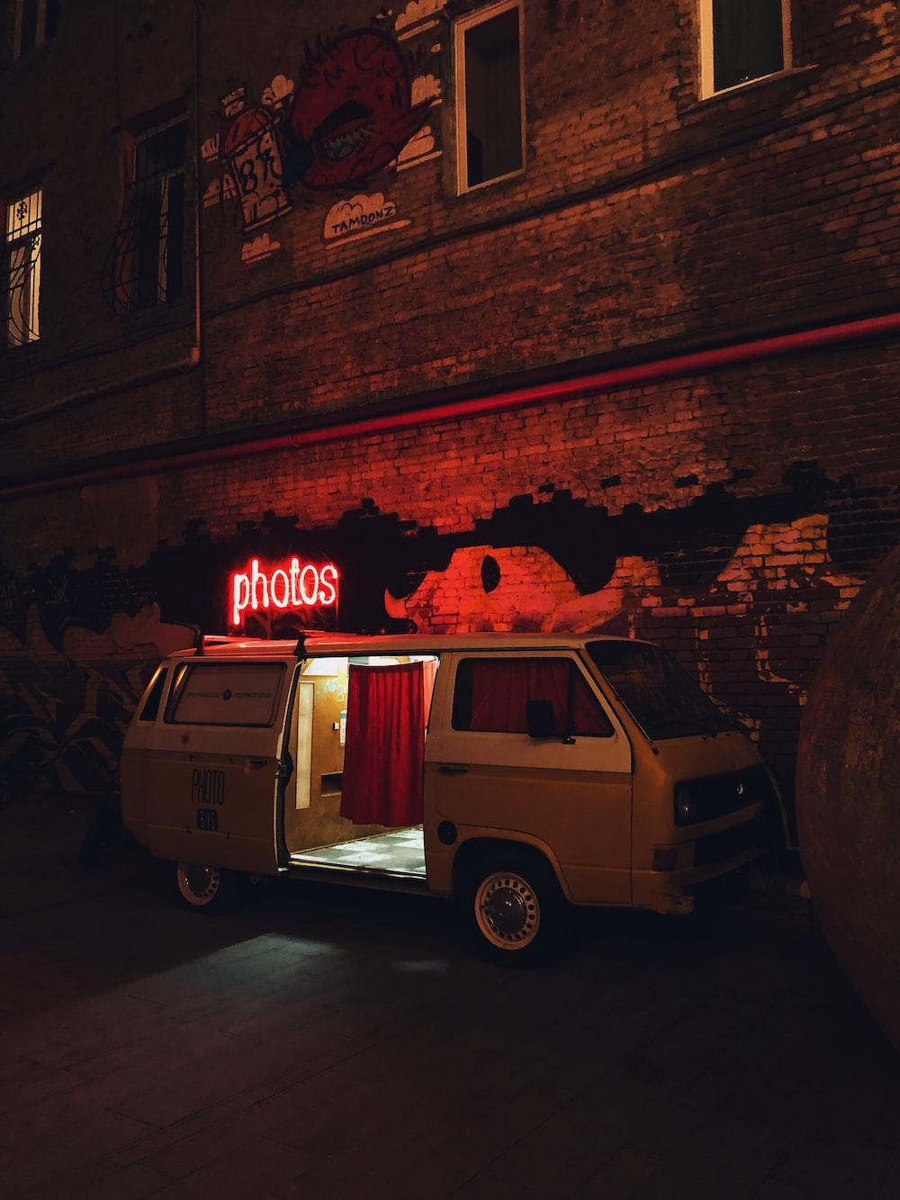 van parking beside wall at night-time