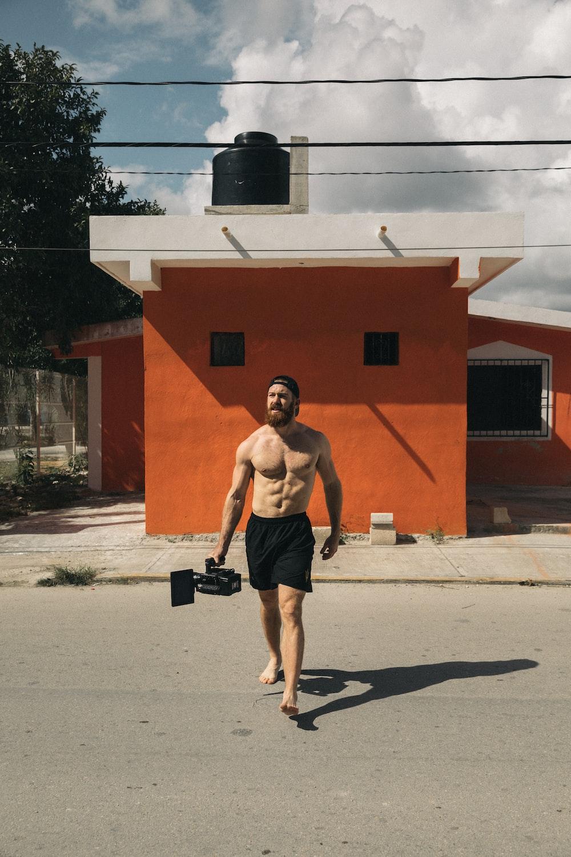 topless man wearing black shorts crossing street during daytime