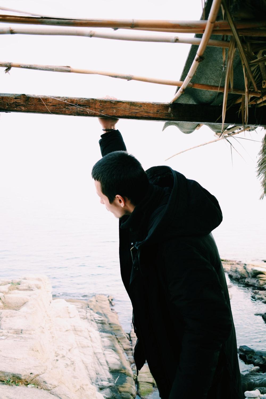 man wearing black hooded jacket during daytime