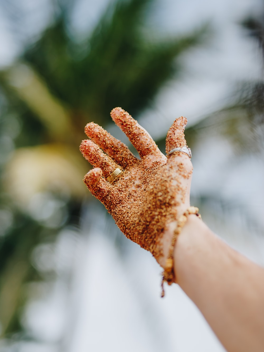selective focus photography of person raising hand covered with brown powder