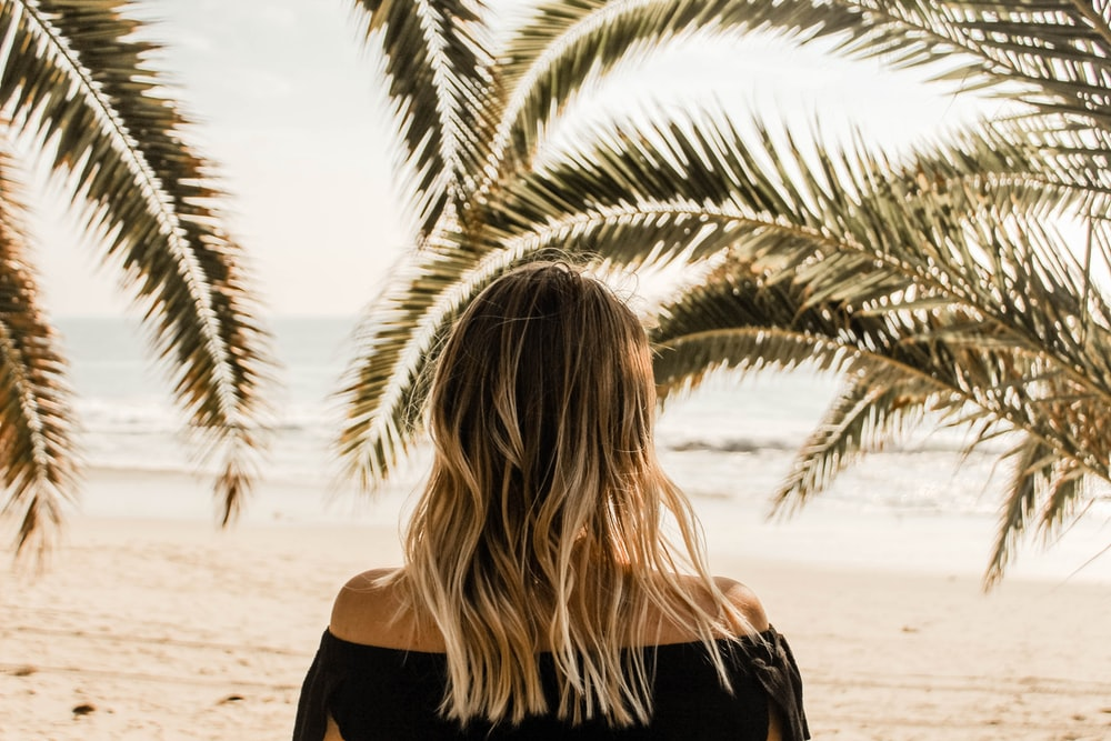 person in black off-shoulder shirt looking at body of water