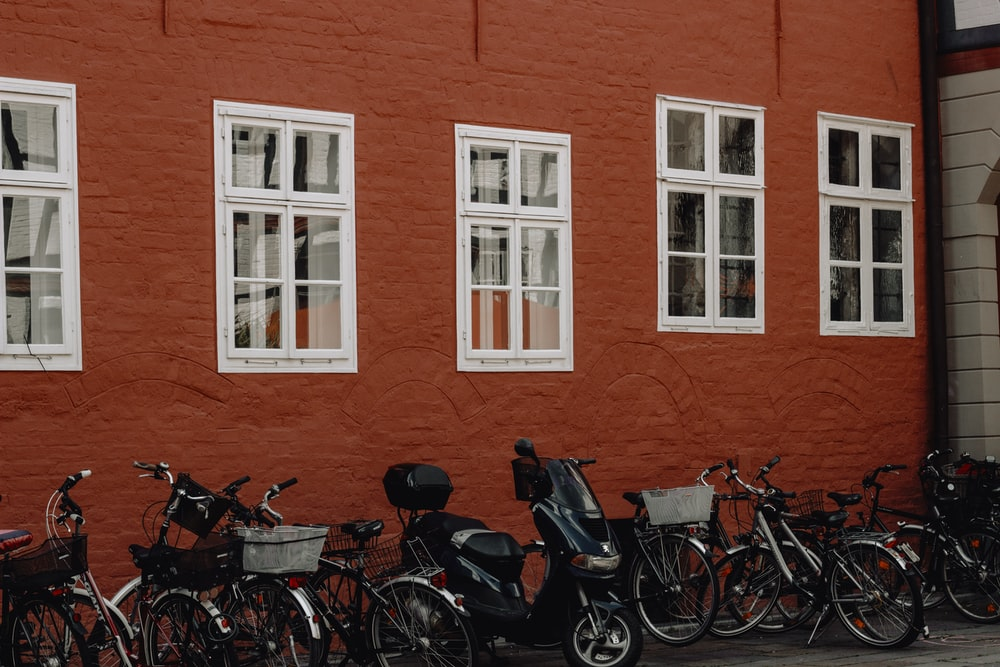 lots of bicycles on park beside red building