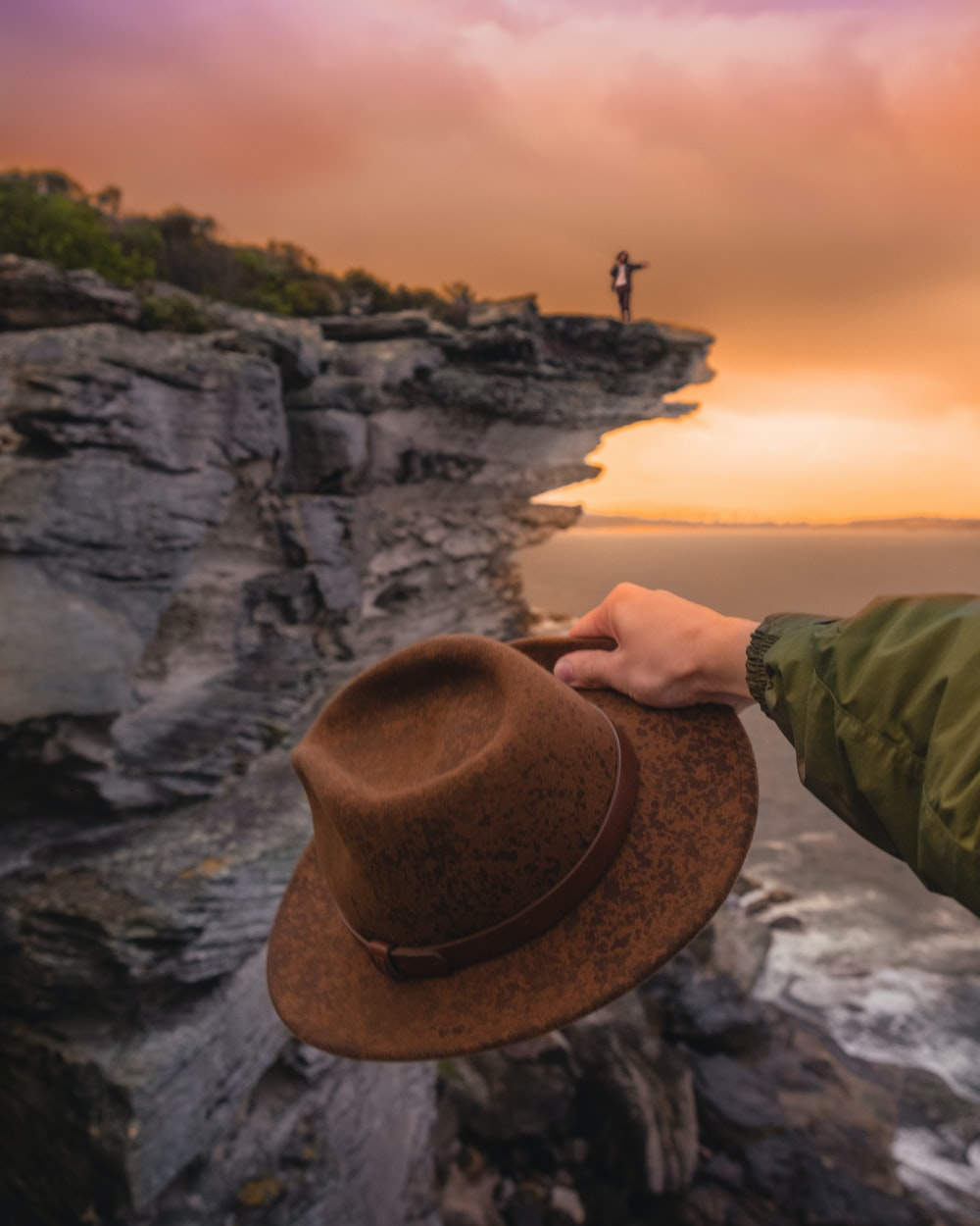 man about to throw his hat at the sea in front of man waving at the edge of the cliff