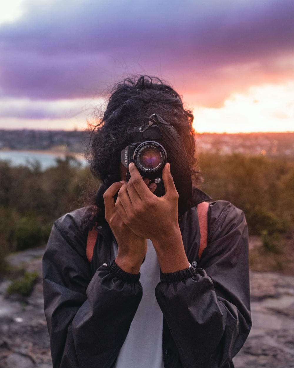 person wearing black jacket taking picture using DSLR camera