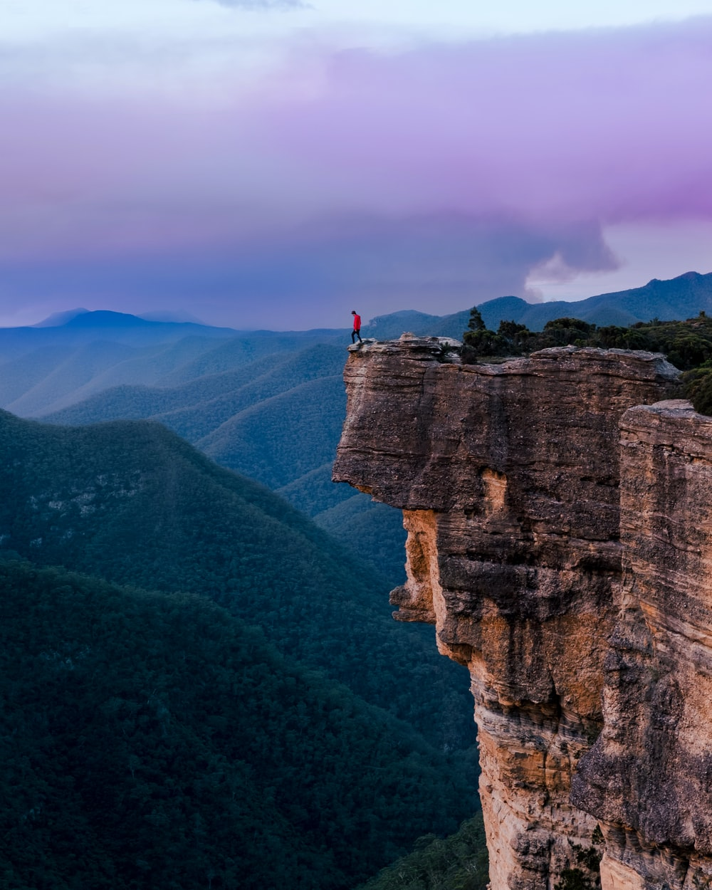 person standing on the edge of a cliff during daytime