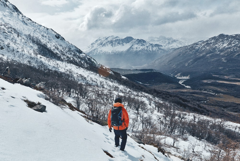 person wearing orange jacket with black pants walking on snow covered field during daytime