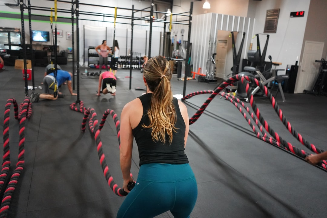 Girl doing crossfit in a bootcamp gym with battleropes