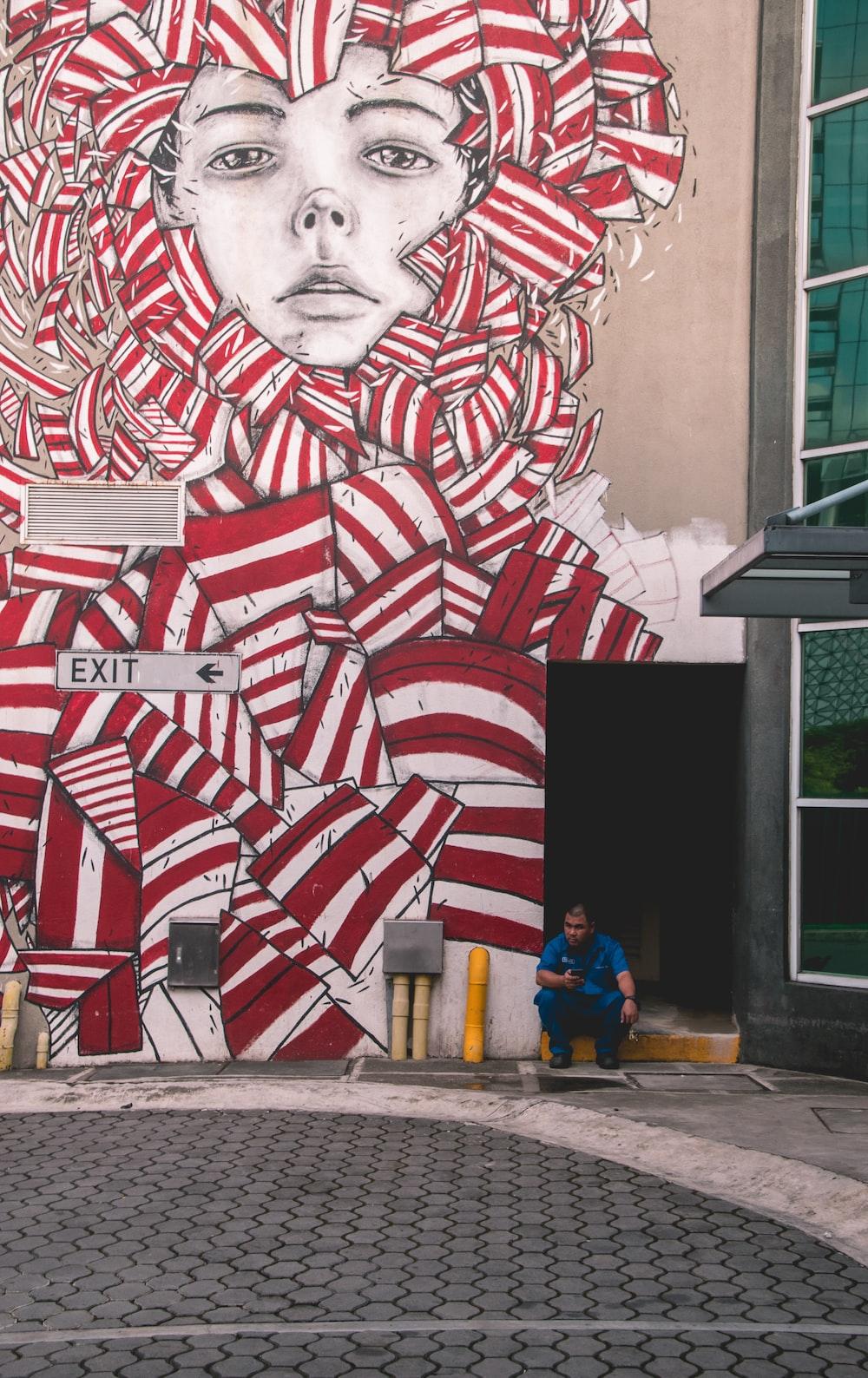 person sitting near wall art