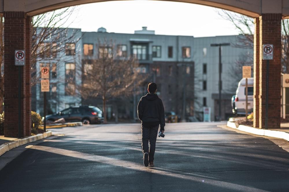 man walking on street near buildings