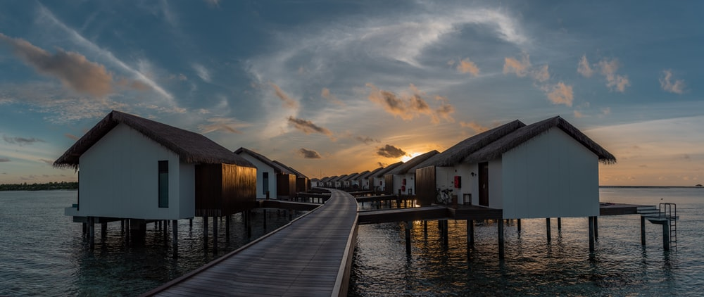 white and black wooden houses at beach during sunset