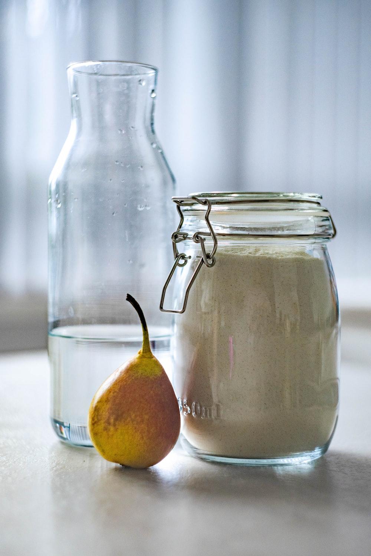 clear glass jar near glass pitcher