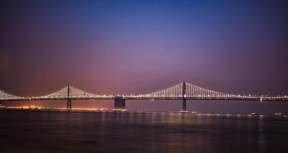 suspension bridge with lights during golden hour
