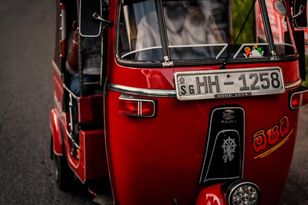 red and black Bajaj auto-rickshaw