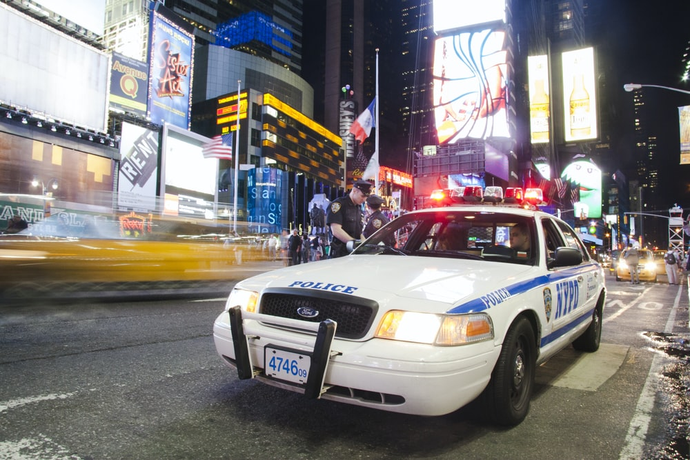white Ford Crown Victoria sedan on road at nighttime