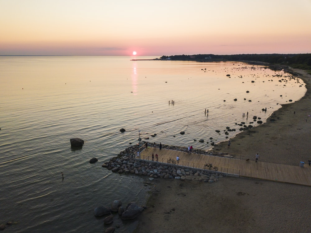 crowd on dock near sea during during sunset