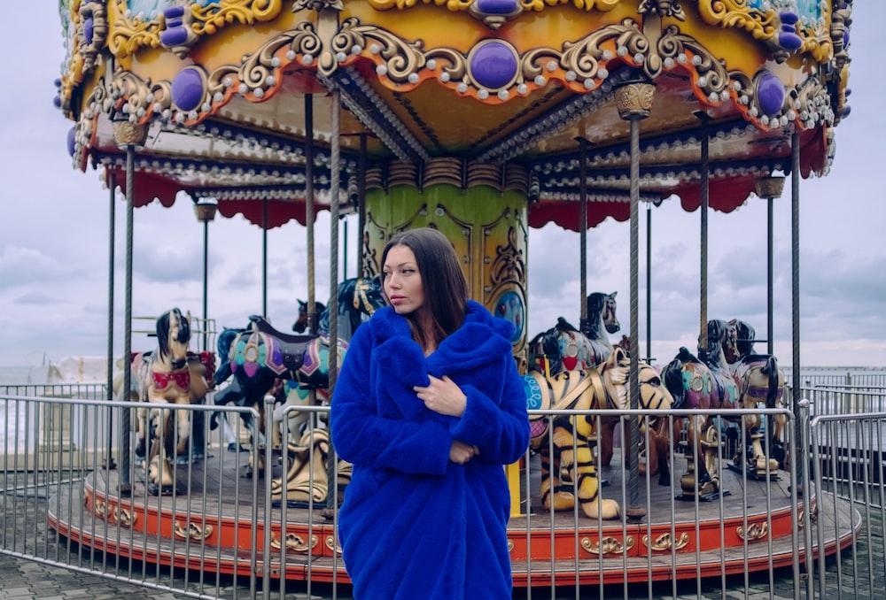 woman wearing blue coat near carousel