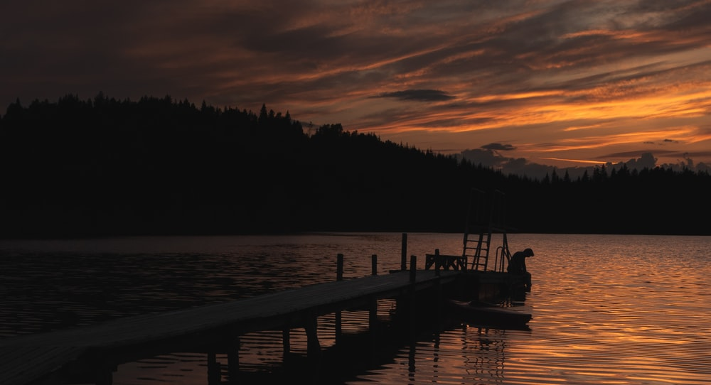 silhouette of dock under orange sky during golden hour