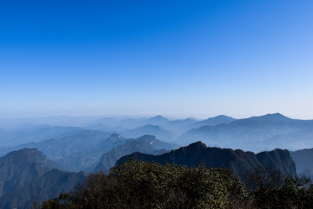 thin fogs covering the green mountain under clear blue sky