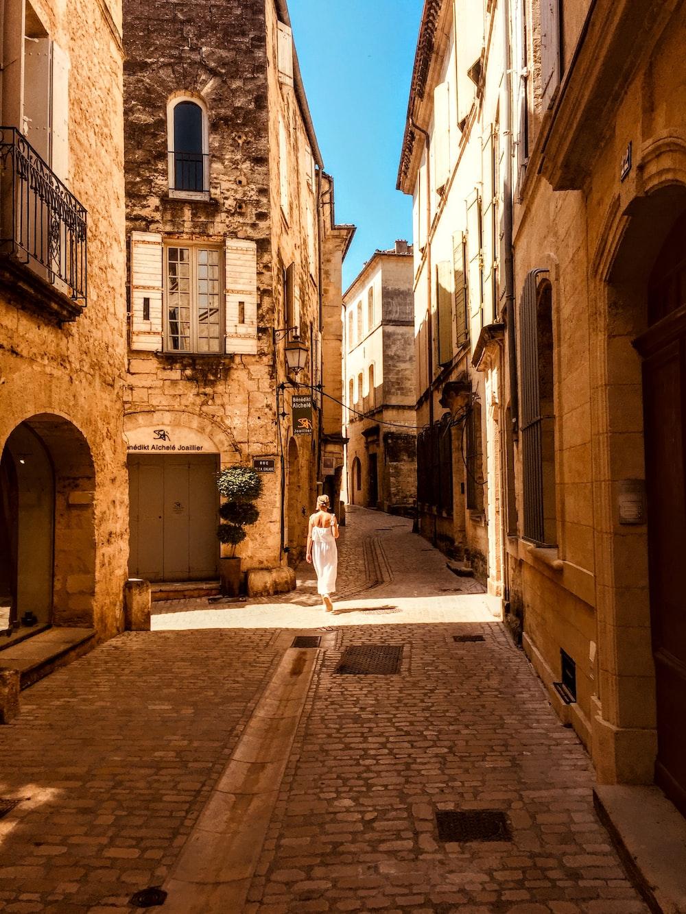 woman walking on narrow pathway during daytime