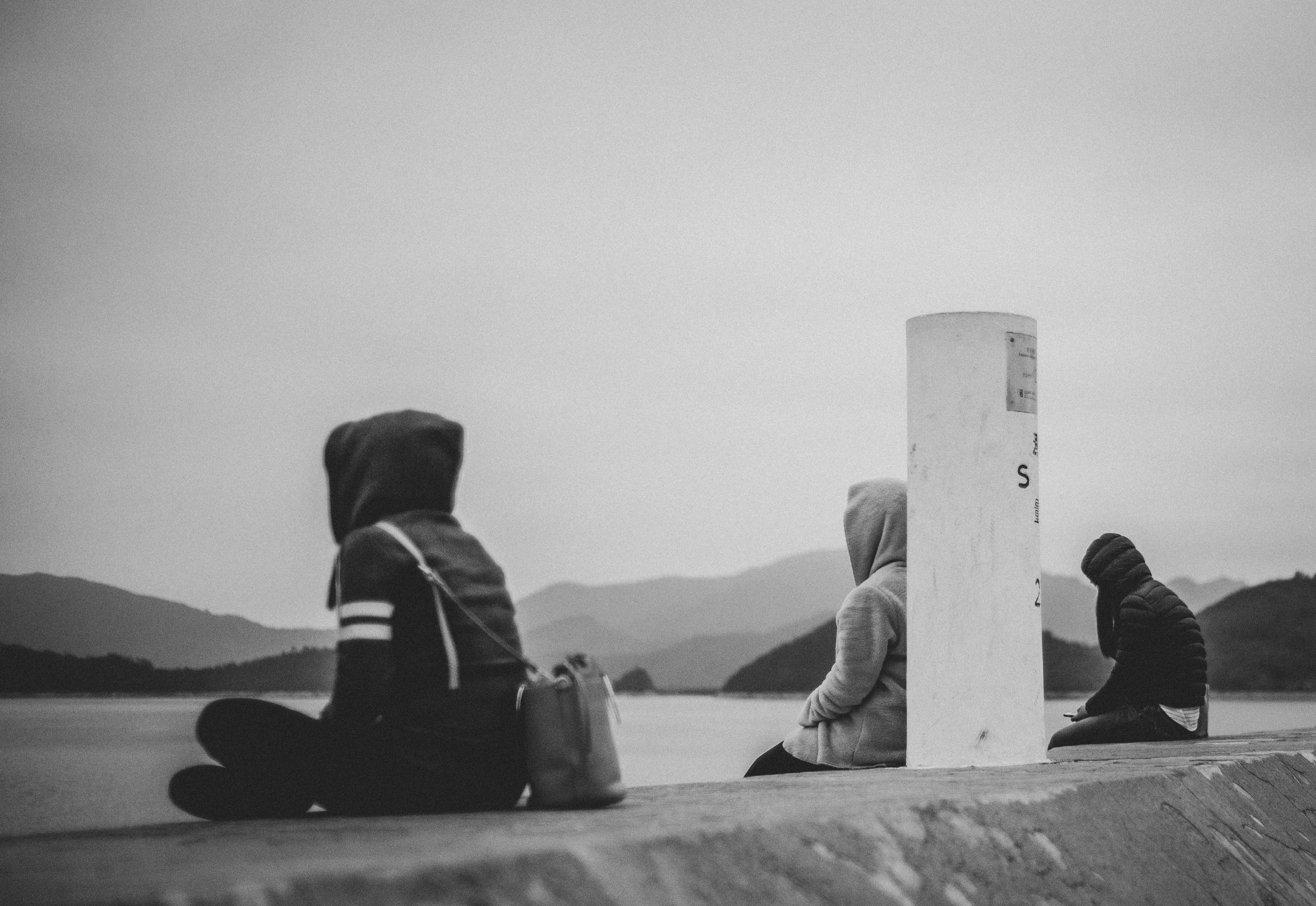 three person sitting near body of water
