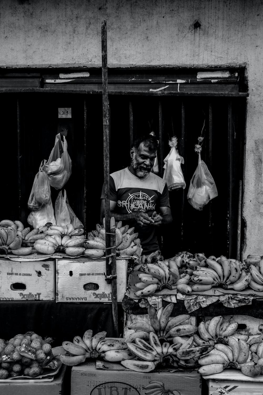 grayscale photo of man standing beside banana fruits