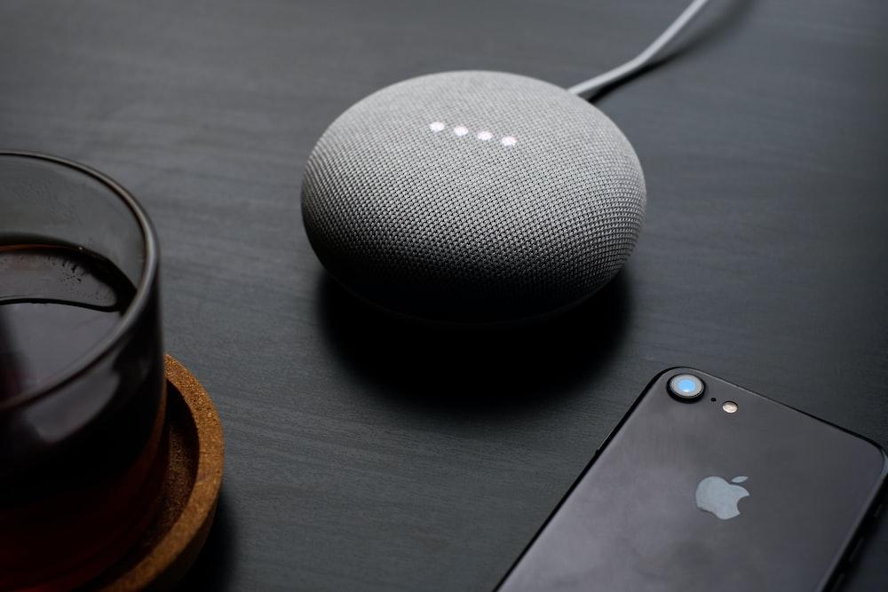 turned-on round gray Google Bluetooth speaker