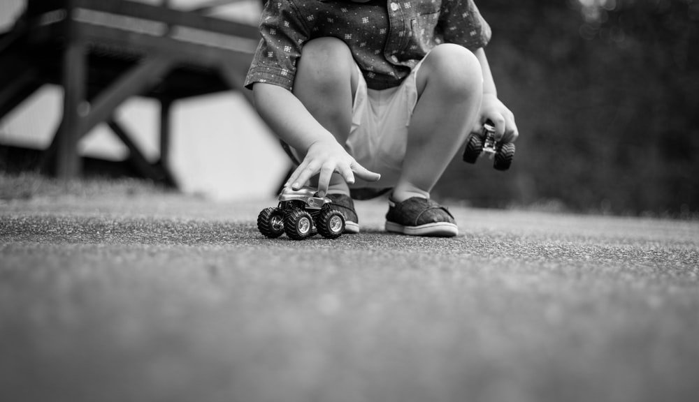 grayscale photography of girl playing car toys