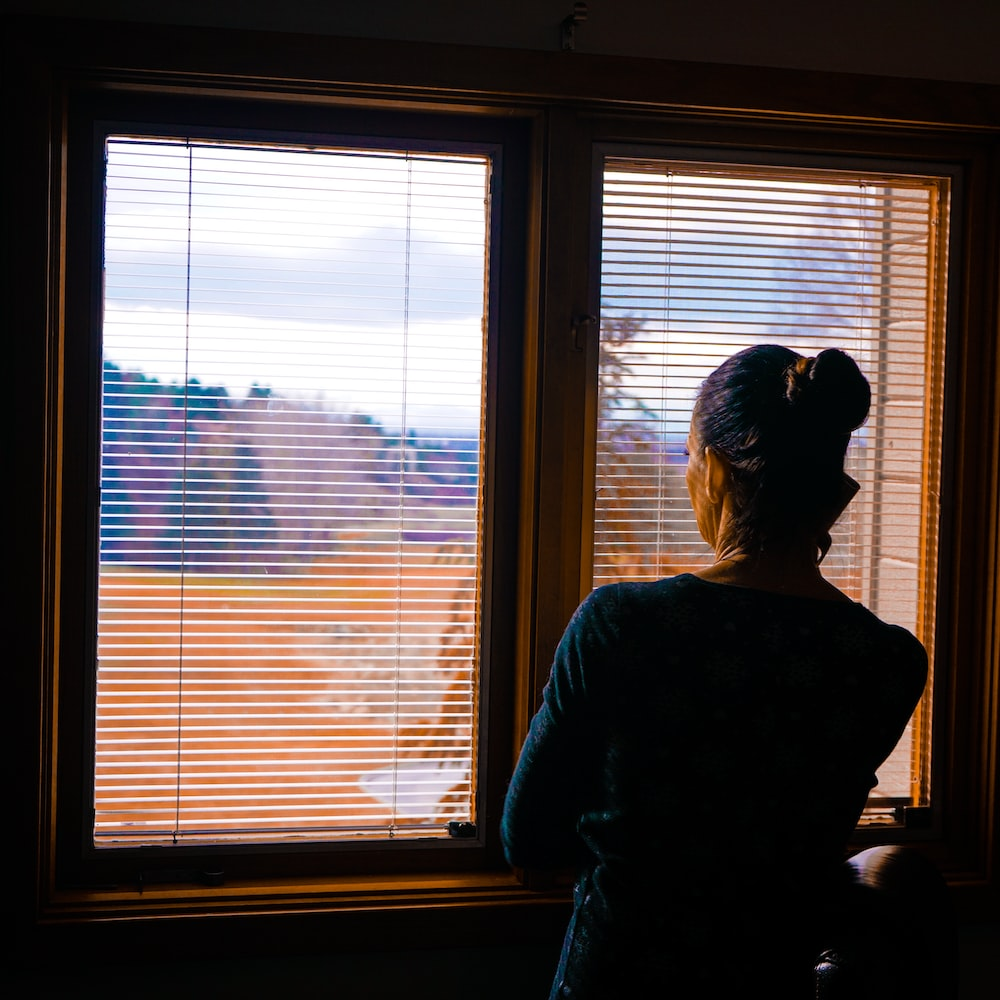 woman standing front of window